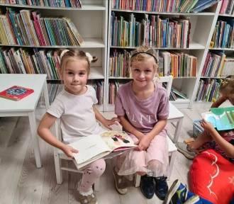 Przedszkolaki wśród regałów z książkami. Pierwsze wizyty w bibliotece