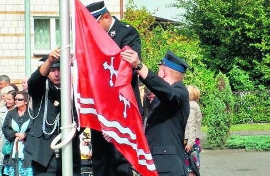 Strażacy podczas wciągania flagi na maszt przed Urzędem Gminy