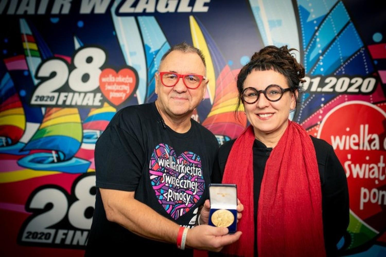 Olga Tokarczuk przekazuje replikę medalu noblowskiego Jurkowi Owsiakowi