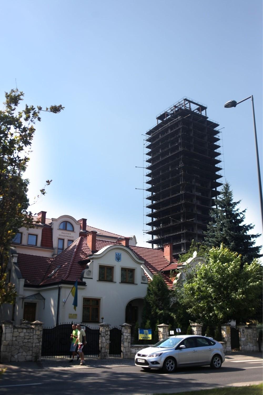 Na drugim planie budynek Salonów Krakowskich przy ulicy Beliny- Prażmowskiego (kremowy), którego część została wybudowana bez odpowiednich zezwoleń