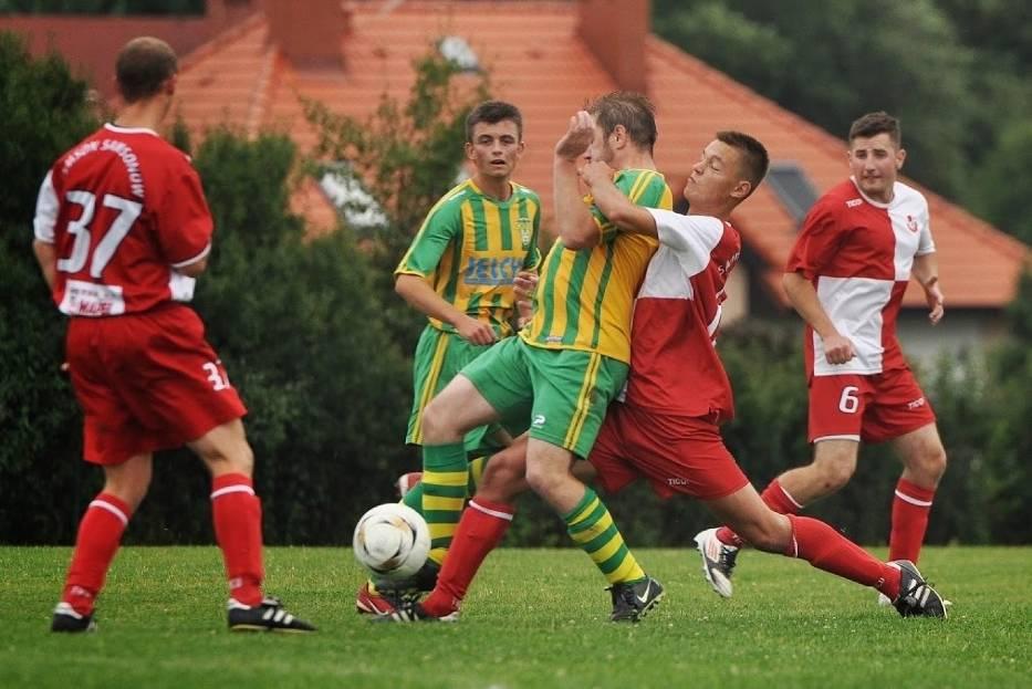 Mateusz Górecki w barwach Samsona Samsonów (biało-czerwony strój) walczy o piłkę z zawodnikiem Grodu Ćmińsk