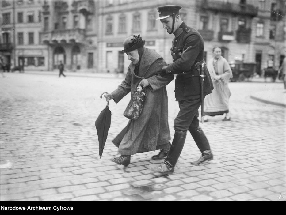 Policjant przeprowadzający staruszkę przez ulicęNa zdjęciu: policjant przeprowadzający staruszkę na drugą stronę Krakowskiego Przedmieścia w Warszawie