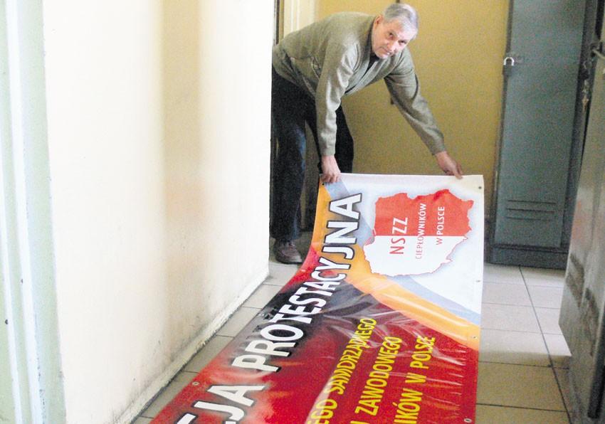Marian Troicki z banerem, który zawiśnie na stacji wymienników ciepła przy ul