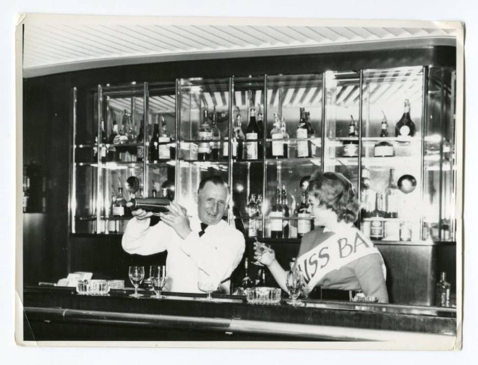 """Miss m/s """"Batorego"""" świętuje za barem w towarzystwie kelnera, przygotowujące go drinki, 1959 r"""