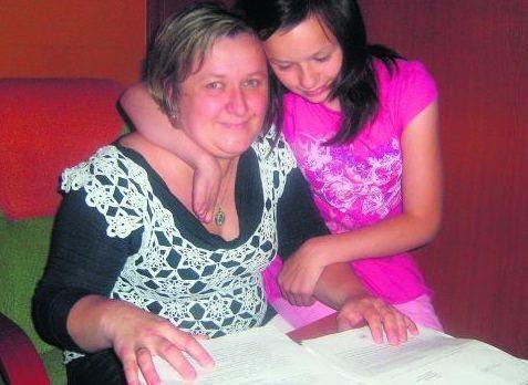 Kinga i Sandra Budzisz ze stertą papierów zebranych przez 12 lat starań  o mieszkanie