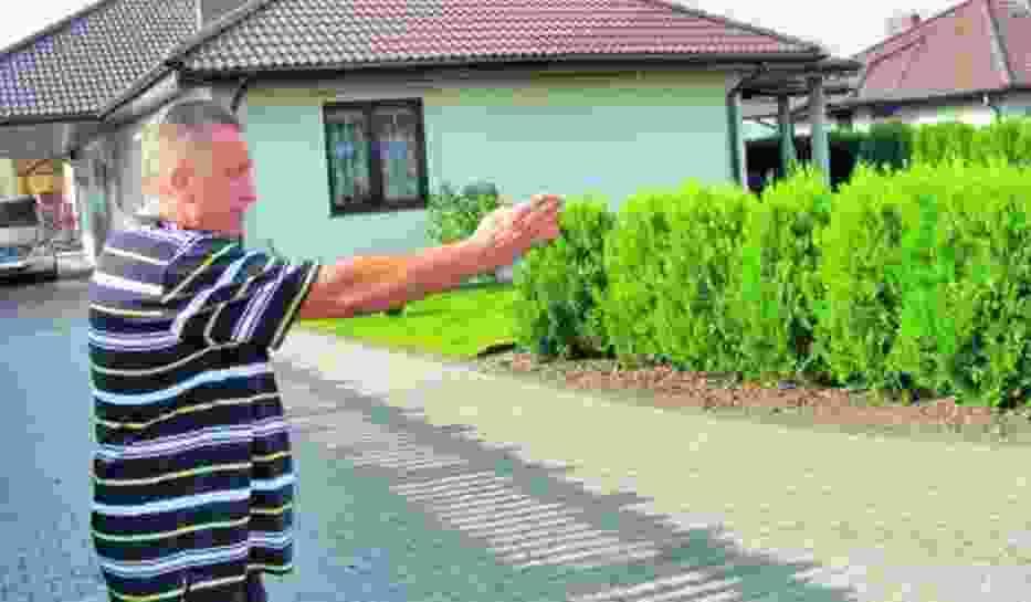 Zbigniew Przymusiński pokazuje, w którym  miejscu na jego działce pojawi się droga