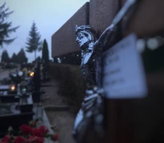 Reklamy firmy kamieniarskiej zatknięte za krzyże na cmentarzu