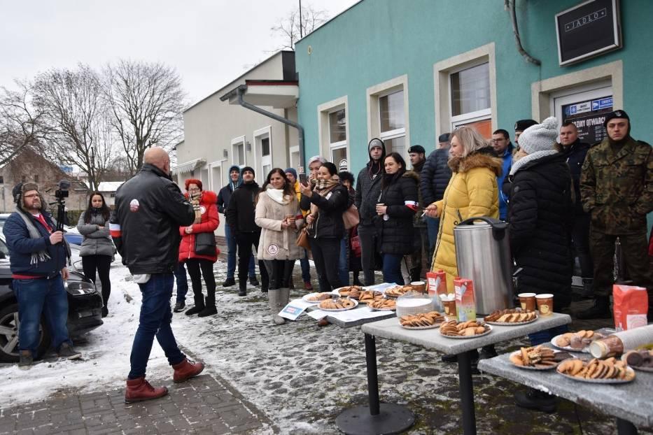 """Grupa patriotyczna """"Nowy Tomyśl się budzi"""" rozdawała przed lokalem ciastka i gorące napoje, zachęcając mieszkańców do wejścia do środka"""