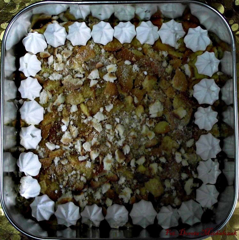 Dno kwadratowej tortownicy (24 cm) wyłożyć grubo pokruszonymi biszkoptami, zwilżyć ponczem (sok z cytryny, kieliszek wódki, wodę i cukier dobrze wymieszać), boki tortownicy obłożyć bezami