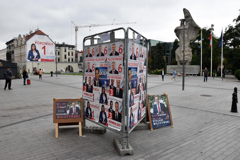 Kandydaci PiS zaklejają się nawzajem na stojaku na ul